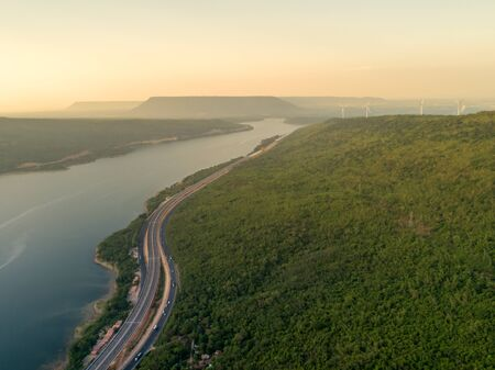 Arial view of highway on passing through the lush greenery tropical rain forest mountain that connected in sunset scenery