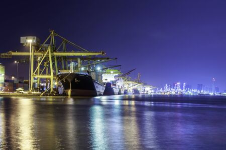 Container cargo ship with ports crane bridge in harbor and refinery industrial at night logistics and transportation concept