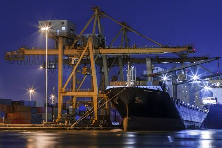 Container cargo ship with ports crane bridge loading dock to terminal in harbor at twilight shipping logistics and transportation concept
