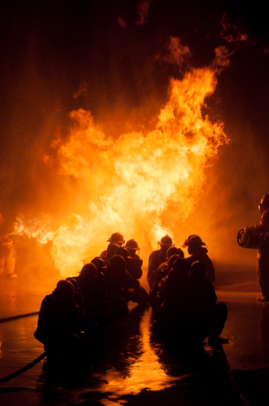 Silhouette of Firemen fighting a raging fire with huge flames of burning timber