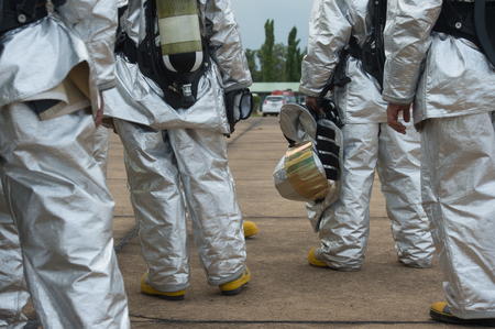 Fire departments & emergency response teams  suited up with PPE to protect them from hazardous materials as they investigate this disaster. Stock Photo