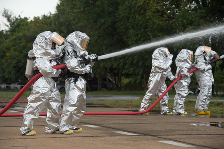 Fire departments & emergency response teams  suited up with PPE to protect them from hazardous materials as they investigate this disaster. 写真素材