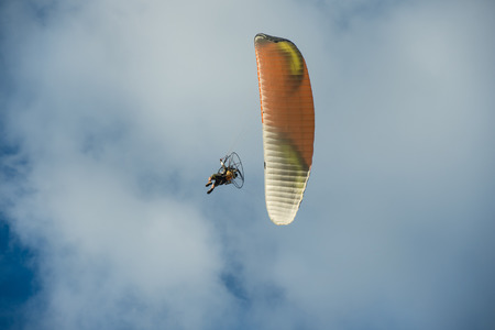 Paramotor flying over the fields in the sky. Standard-Bild
