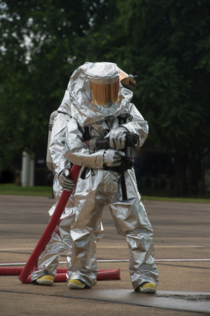 protective suit: Fire departments & emergency response teams  suited up with PPE to protect them from hazardous materials as they investigate this disaster. Stock Photo