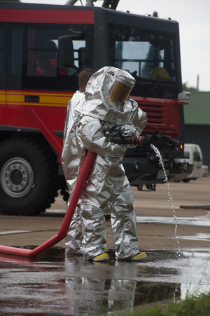 radiation protection suit: Fire departments & emergency response teams  suited up with PPE to protect them from hazardous materials as they investigate this disaster. Stock Photo