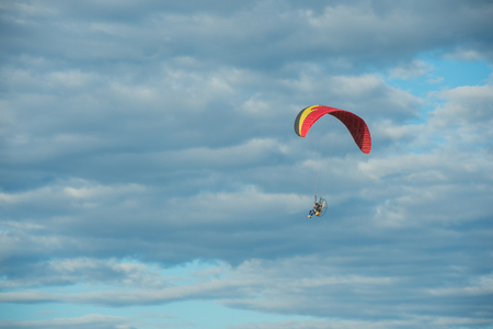 Paramotor flying over the fields in the sky. Stockfoto