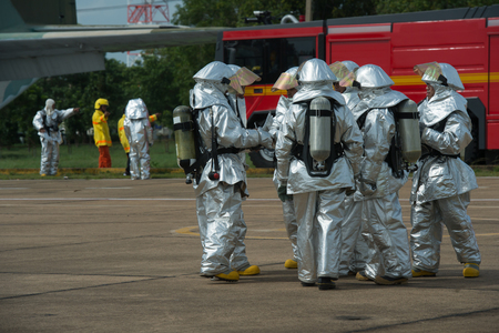 self contained: Fire departments & emergency response teams  suited up with PPE to protect them from hazardous materials as they investigate this disaster. Stock Photo