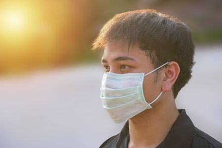 Asian man wearing the face mask due to air pollution - Young adult on park with Pollution mask - person protecting from air contamination or coronavirus or covid-19 by wearing mask.