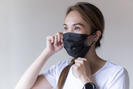 Asia woman wearing a black face mask to deal with virus or pollution.