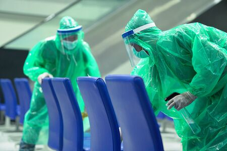 medical officers wearing rain cover, mask, glove, and plastic shield cleaning airport area to protect corona virus