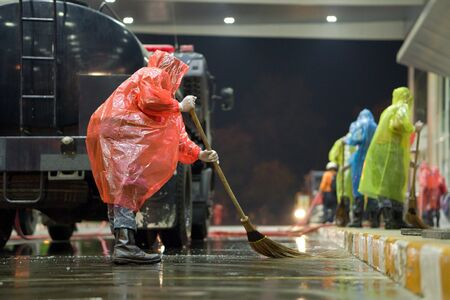 solders wearing rain cover, mask, glove, and plastic shield cleaning airport area to protect corona virus Banco de Imagens