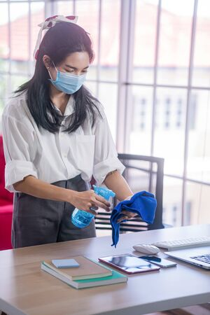 young asian woman cleaning her computer desk and equipment to protect covid19 virus infection