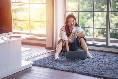 top view of young asian woman working with laptop computer in the living room. Work from home and study at home concept.