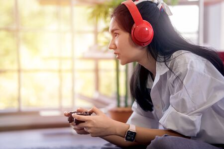 young asian woman enjoy her media gaming in the living room