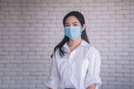 beautiful young asian woman wearing face mask to protect covid19 virus against white brick wall Stockfoto