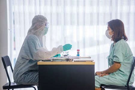 Asian Female Patient Being Reassured By Woman Doctor In Hospital Room