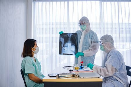 Asian doctor in personal protective equipment or ppe explain the x-ray film of covid-19 or coronavirus infection to patient in the hospital. coronavirus, covid-19 outbreak, or medical hospital concept Stockfoto