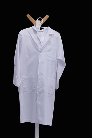 white medical gown hanging on wooden hanger isolated on black background Stockfoto