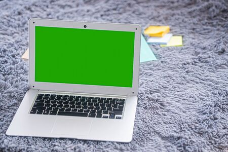 lap top computer with green screen on gray carpet
