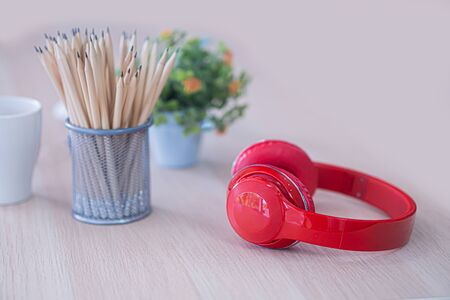 the red head phone and pencil case on white table
