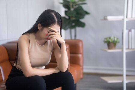 An Asian woman is stressed in the psychiatrist's room.