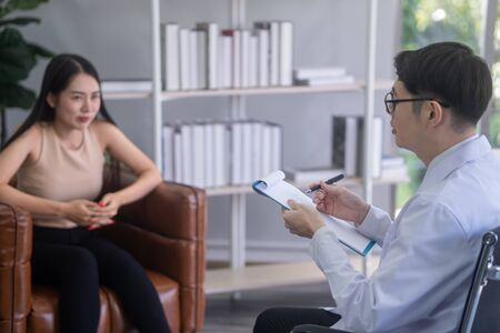 The psychiatrist is advising stressful asian female patients. 写真素材