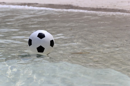 Soccer ball on sea water. photo