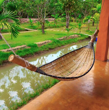 View of nice hammock hanging between two pillar. Stock Photo