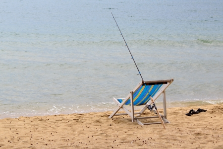 Fishing rod is placed beside the chair beach  photo