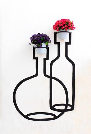 jardineras: collage de flores de geranios en macetas en la pared Foto de archivo