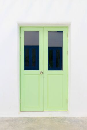 Green elegant entrance door with white wall.