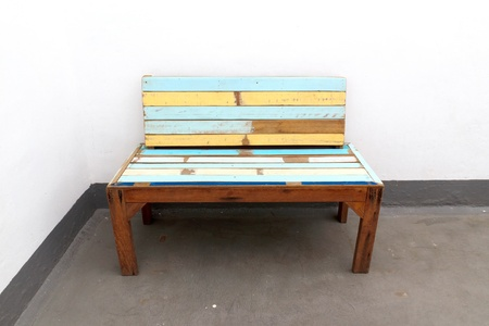A old wooden chair with white walls.