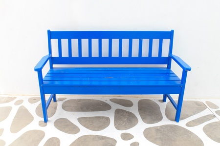 A blue wooden chair with white walls