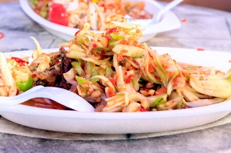 A spicy mango salad with fried fish. photo