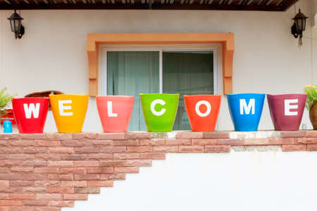 Welcome sign, at colorful pots with sort rows.  photo