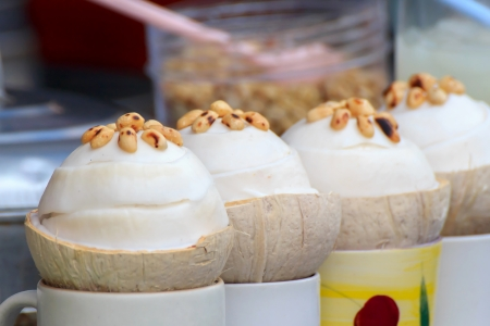 Coconut ice cream in coconut shell and topped with roasted peanuts.
