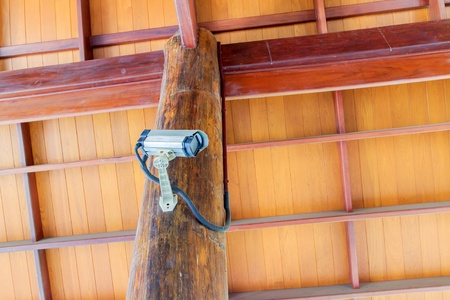 A CCTV camera on pillar of a wooden Thai pavilion. photo