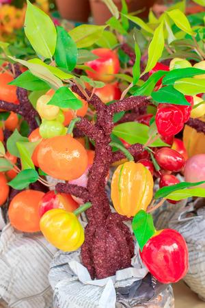 Many fake fruit hanging on the fake tree. photo