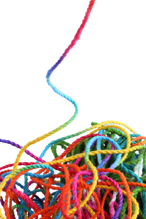Tangled colorful sewing threads on white background.