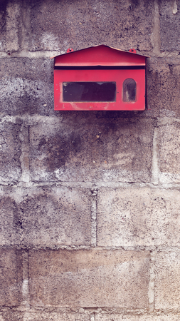 Old red mailbox on concrete wall. Vintage effect. Stock Photo