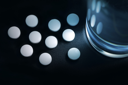white pills placed near the glass of water on the bedside table, insomnia. Stock Photo