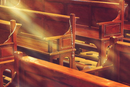 old church: wooden church pews in church and rosary beads with sunlight