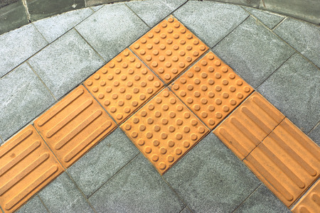 braille block tactile paving for blind handicap on tiles pathway Stock Photo - 73509660
