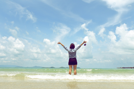 young woman with arms apart on sand beach with blue sky and white cloud, relaxing holiday.