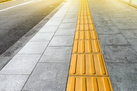 Tactile paving for blind handicap on tiles pathway, walkway for blindness people. Stock Photo