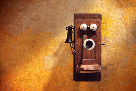 Antique Wall Telephones on dirty yellow wall