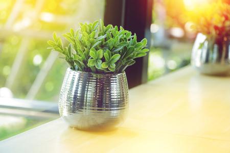 Plastic Leaves Of Small Tree In Aluminum Vase On Table Near Windows