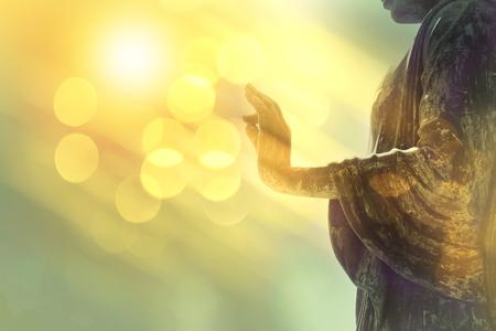 hand van Boeddhabeeld met gele bokeh achtergrond, licht van wijsheid en concentratie concept