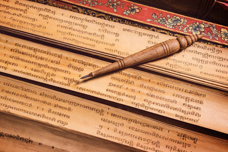 Bangkok, Thailand - November 8, 2018 : pen for writing text on Bai Lan background, Bai Lan or ancient palm leaf manuscripts content about buddhist scriptures, Pali language Khmer 写真素材