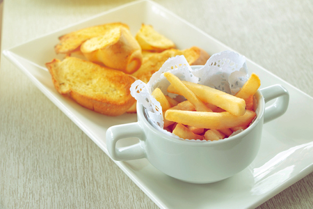 close-up of french fries in cup with garlic bread on wood table in restaurant Banco de Imagens